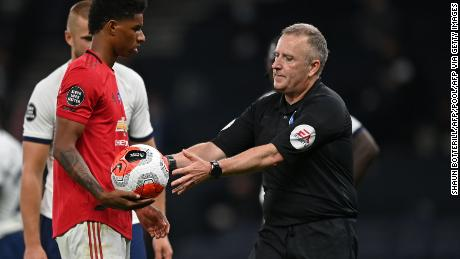 Referee Jonathan Moss takes the ball from Marcus Rashford after wrongly awarding a penalty.