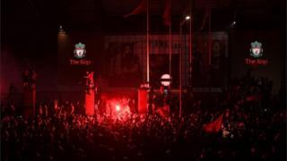 Fans celebrate Liverpool winning the Premier League title outside Anfield stadium