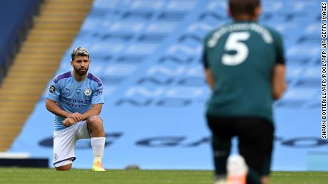 Manchester City striker Sergio Aguero(L) and Burnley defender James Tarkowski take a knee in support of the Black Lives Matter movement.