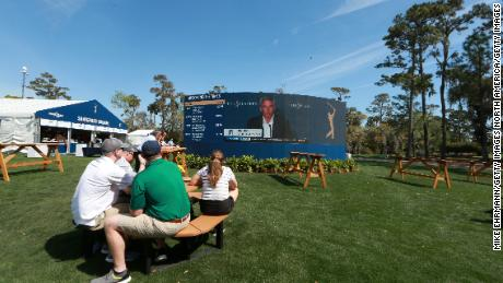 Fans watch on video screens as Monahan speaks to the media in a press conference announcing fans will no longer be allowed to attend PGA tour events.