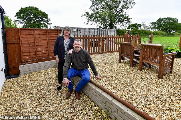 Devastated: David and Rebecca French next to the wall which marks the boundary between their five foot garden and the rest of the land owned by an adjacent farm