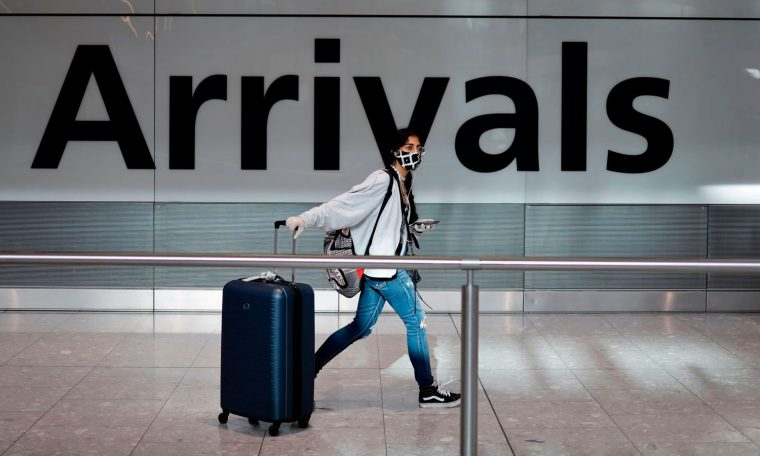 A passenger wearing a face mask as a precaution against the coronavirus arrives at Heathrow airport