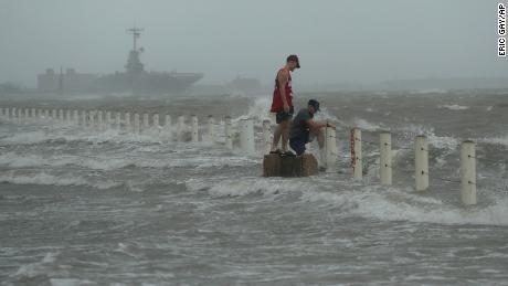 Two men stand near a sea wall as Hurricane Hanna makes landfall.