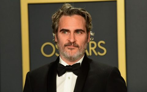 Joaquin Phoenix smiling slightly, looking to the side