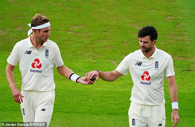 Anderson takes the ball from new-ball partner Stuart Broad during the first Test in Manchester