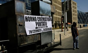 """A man stands near the prototype of a mobile crematorium with a banner reading """"Mobile crematorium, Made in Bolivia"""", built by a local engineer to alleviate the backlog of bodies at local crematoriums, in La Paz, Bolivia 4 August 2020."""