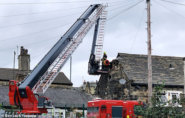 Pictured are fire officers inspecting the damage to the two-storey property in Bradford