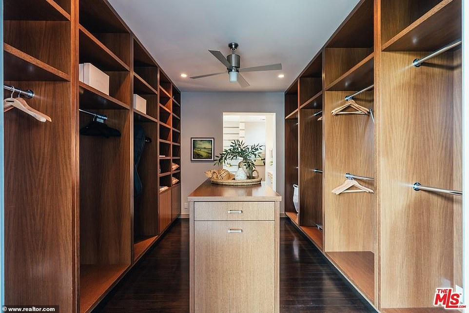 Clothes minded:A dark wood walk-in closet is every girl's dream with dark floors and an island perfect for storing costume jewelry and fancy purses
