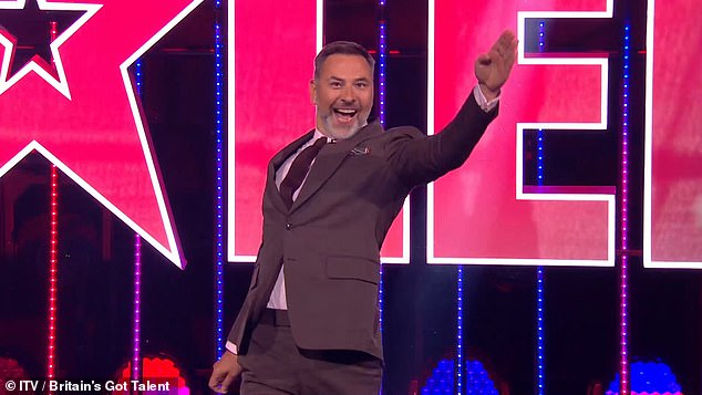 Arriving: David Wallims arrives on stage behind a wall of wings for the boys singer: 'Our David should always be underestimated'