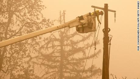 Workers continue to repair the electrical system following the Beech Creek fire through a fishermen's band recreation site in Mill City, Oregon.