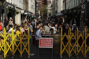 People react to being photographed as they sit outside on a street closed to traffic, so bars and restaurants can continue to open on Saturday, September 19, 2020 in the Soho area of ​​central London.  The latest lockout restrictions appear to be in place across the UK.  On the cards, as the British government targeted other areas on Friday in an effort to stem the rapid rise in new coronavirus infections.