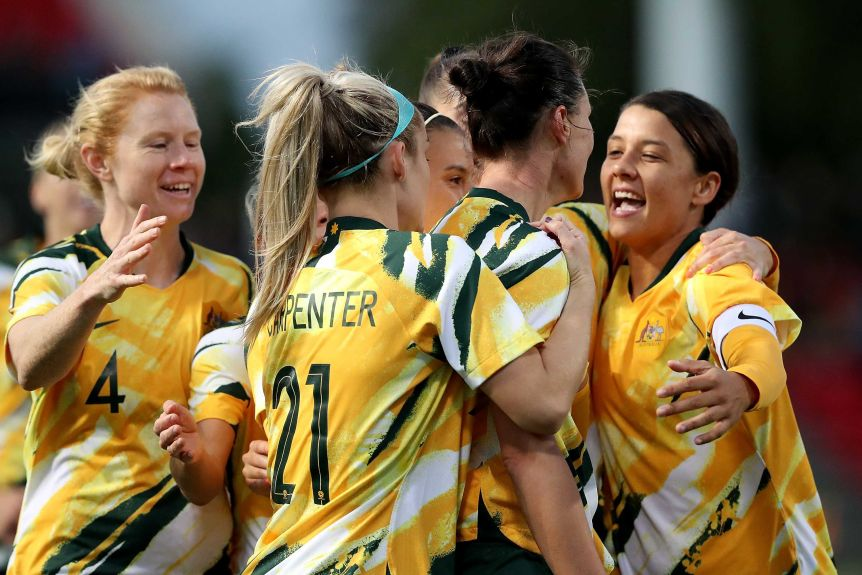 Many Matildas players hug and smile in celebration.