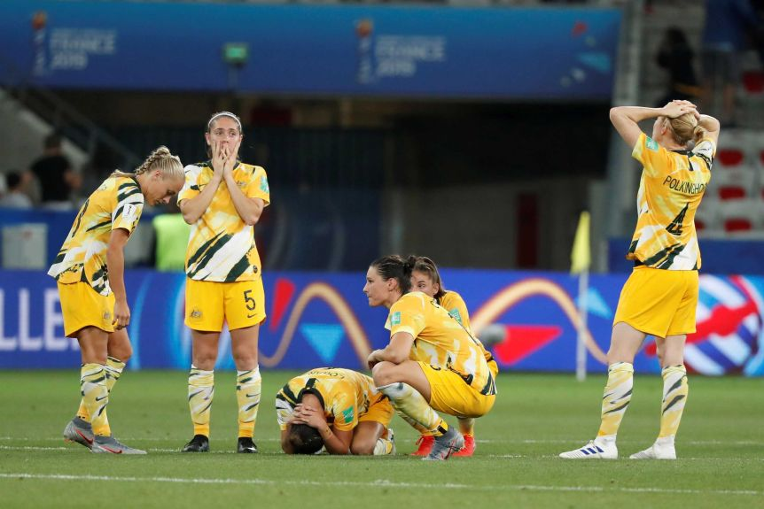 A group of international footballers kneel on the ground after losing the World Cup.