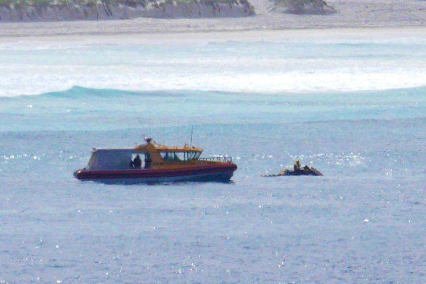 A search boat and a Jetsky resume the search for a missing person, sand dunes in the background.