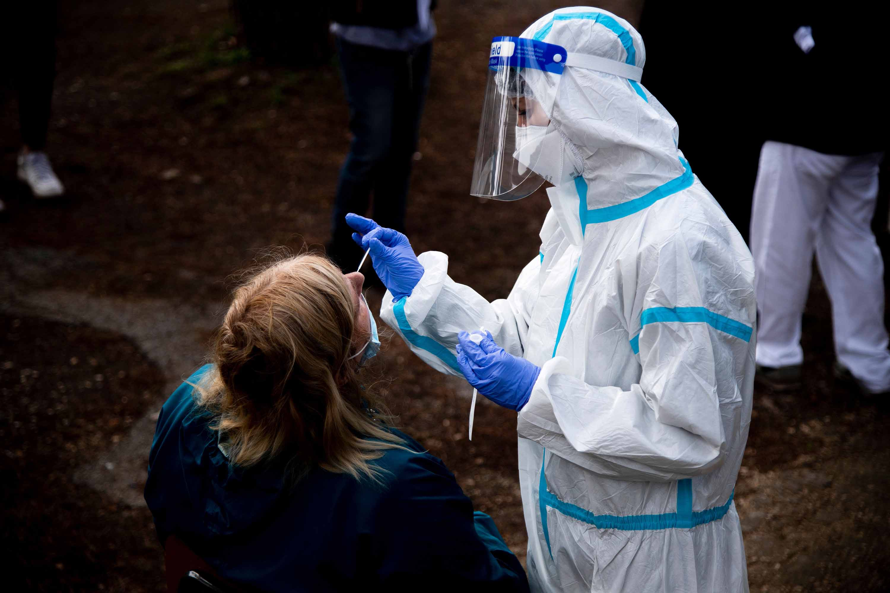 A woman undergoes a swab test for coronavirus on October 12 at a drive-thru testing site at a hospital in Rome.