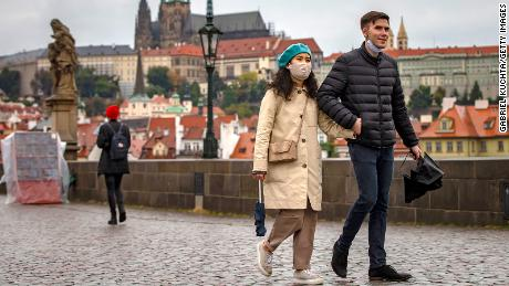 Visitors cross the medieval Charles Bridge in Prague as the Czech Republic experiences record growth after lowering its numbers.