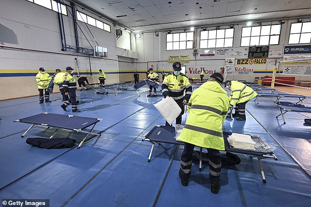 Civil protection staff prepares field hospital beds for potential COVID-19 patients in Tinin, Italy on Thursday.