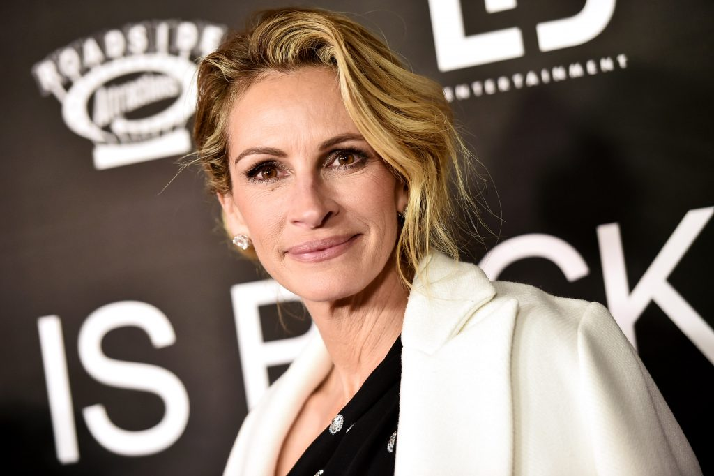Julia Roberts smiles in front of a black background