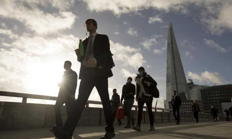 Commuters cross London Bridge in view of The Shard in London on November 2 ahead of a partial lockdown in UK.