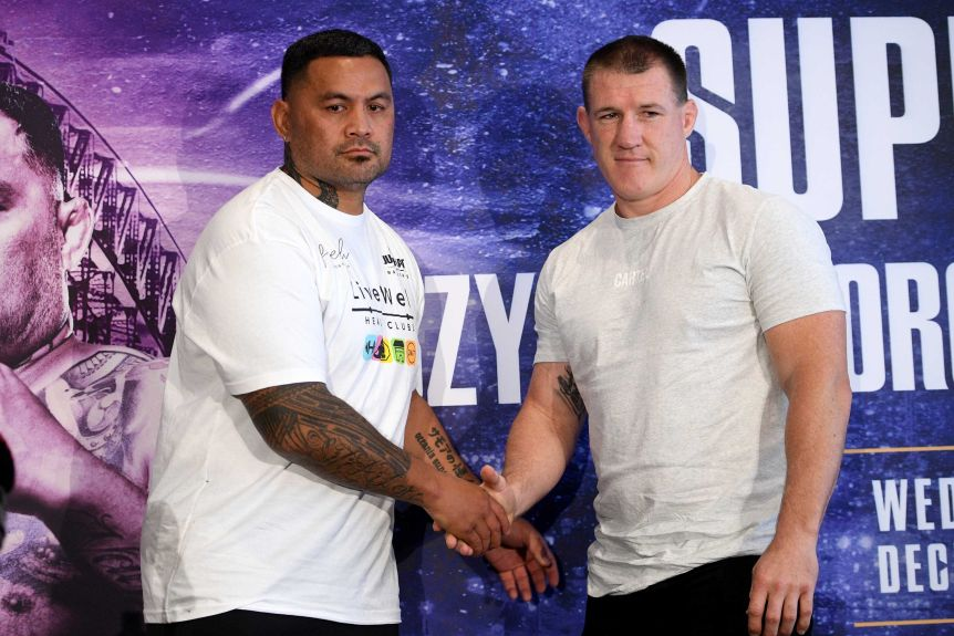 Mark Hunt and Paul Galen stand and shake hands, both wearing white T-shirts against a blue background.