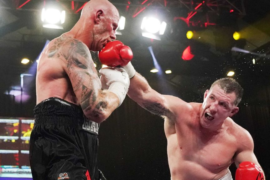 A boxer bends over to punch his opponent in the ring