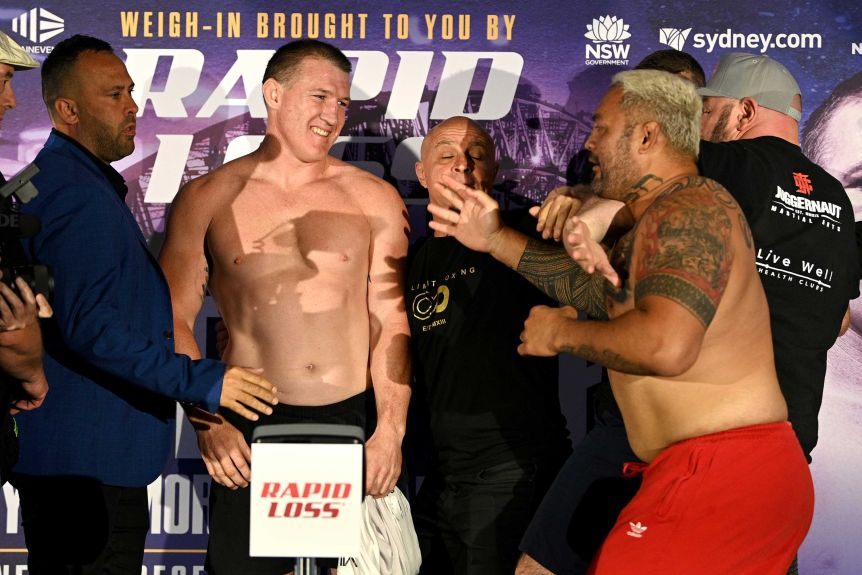 Paul Glenn smiles at Mark Hunt as he is held back by mindful thinkers before the boxing match.
