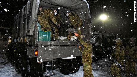 Japanese Self-Defense Forces personnel prepare food and water for those stranded on the Kanetsu Expressway on December 17.