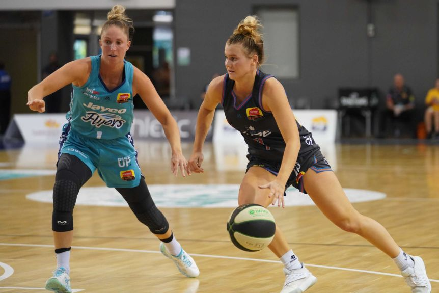 Tasnusville Fire WNBL player dribbles the ball with his left hand against the Southside Flyers.