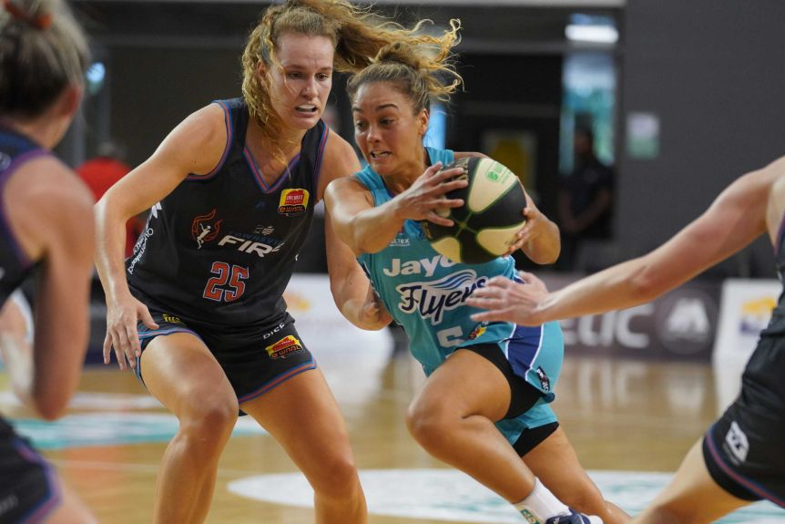 A South Tside Flyers WNBL player runs to the basket, being rescued by the Townsville Fire.