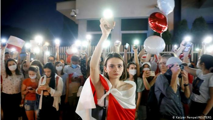 Woman wrapped in white and red flag with her hand, holding cellphone with light