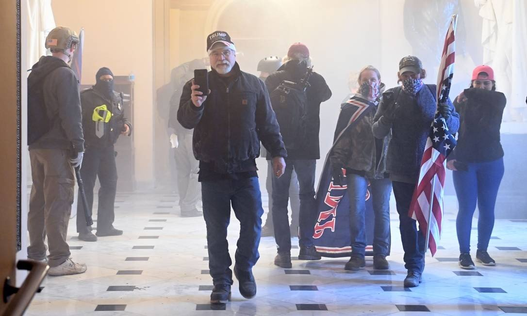 Supporters of President Donald Trump enter the Capitol as tear gas takes over building corridors Photo: SAUL LOEB / AFP