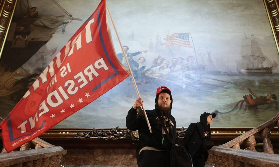 A defender holds a flag of support for President Trump inside the US Capitol building, near the Senate Chamber: Win MCNAMEE / AFP