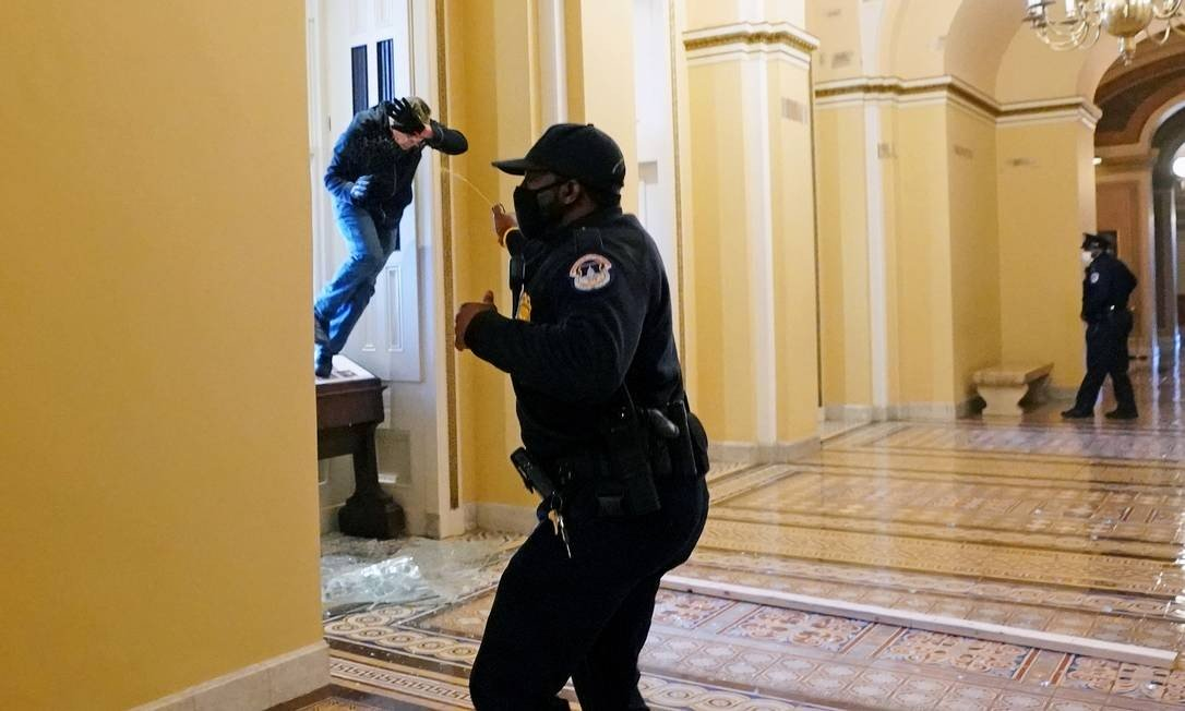 A Capitol police officer throws pepper spray at a guard who tries to enter the Congress building Photo: POOL / REUTERS