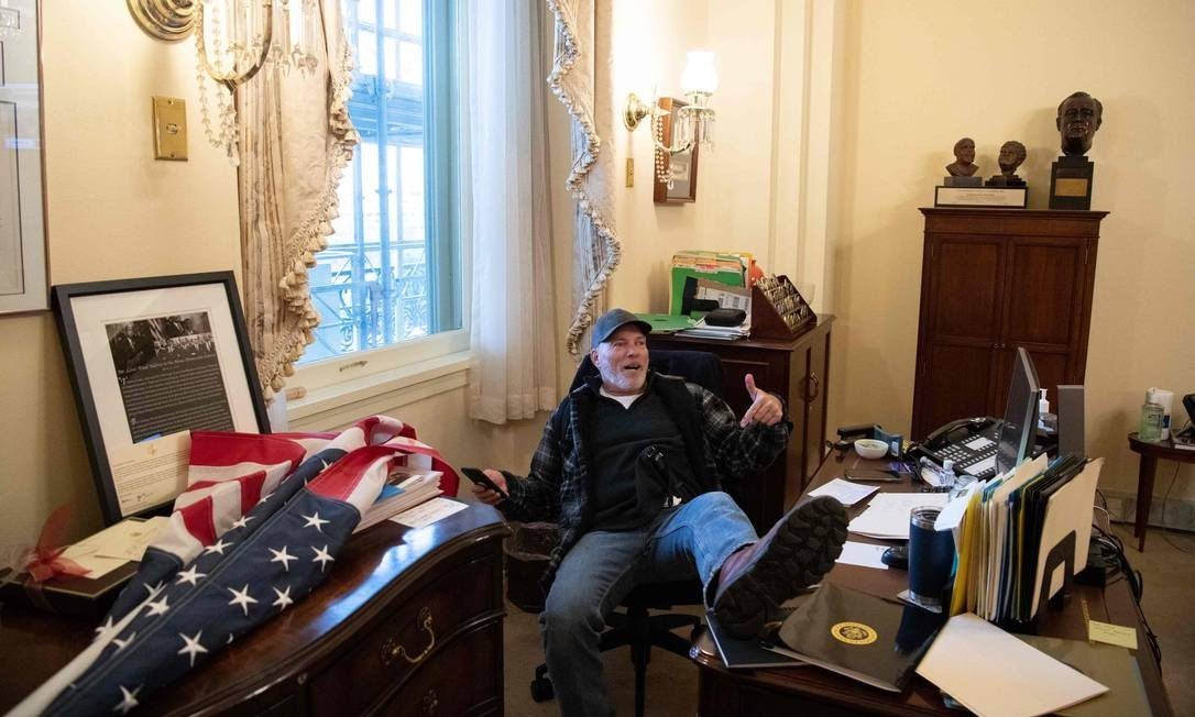 A protestor sits in Mayor Nancy Pelosi's office during an invasion of the Capitol Building Photo: SAUL LOEB / AFP