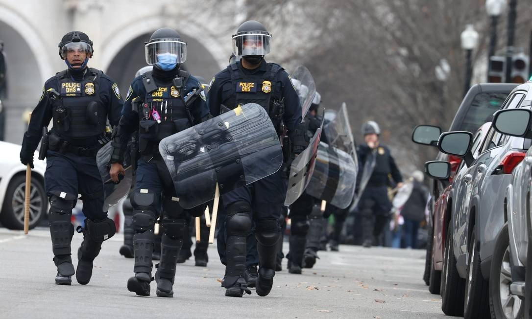 Police officers in riot suits walk towards the US Capitol while protesters attack the building Photo: TASOS KATOPODE / CP