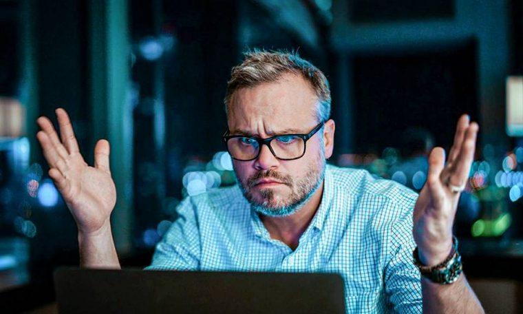 Homem frustrado em frente ao computador