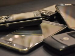 Some old cell phones and smartphones are on a table