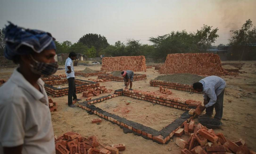 Construction of incineration platforms on the ground next to Sarai Kale Khan crematorium in New Delhi