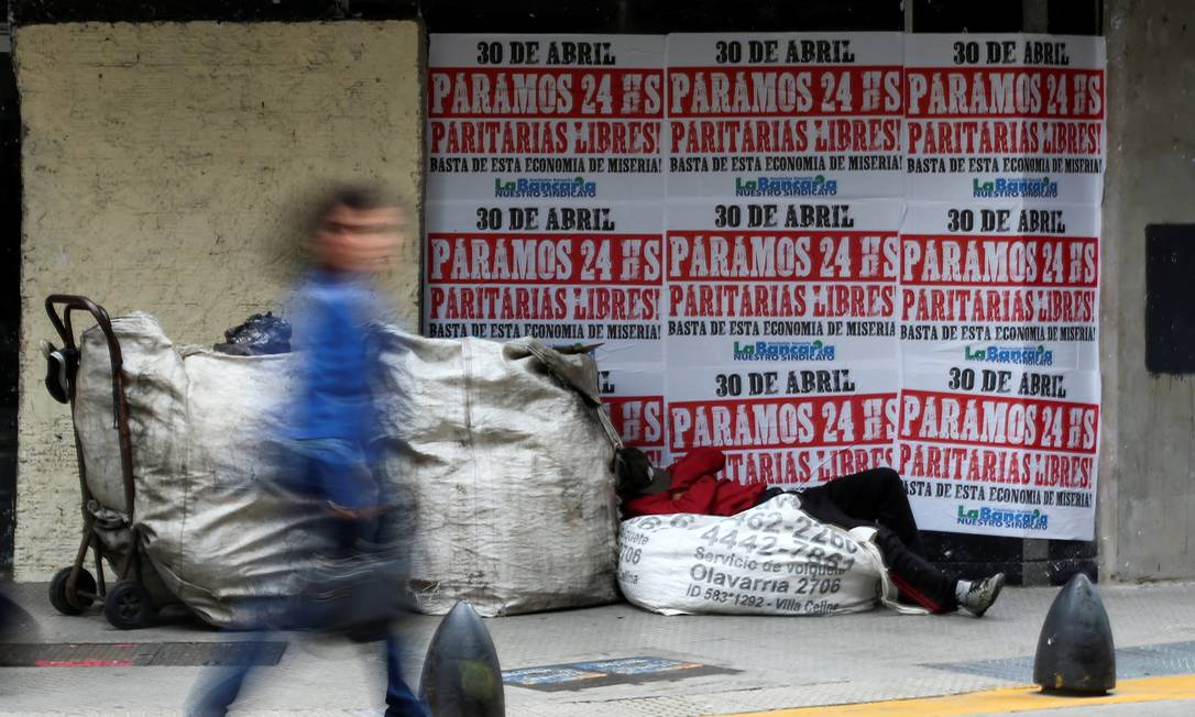 The homeless man sleeps outside a currency exchange with posters announcing the general strike in April 2019;  Since 2018, the country is experiencing a cocktail of increases in the dollar, interest rates, inflation and unemployment.