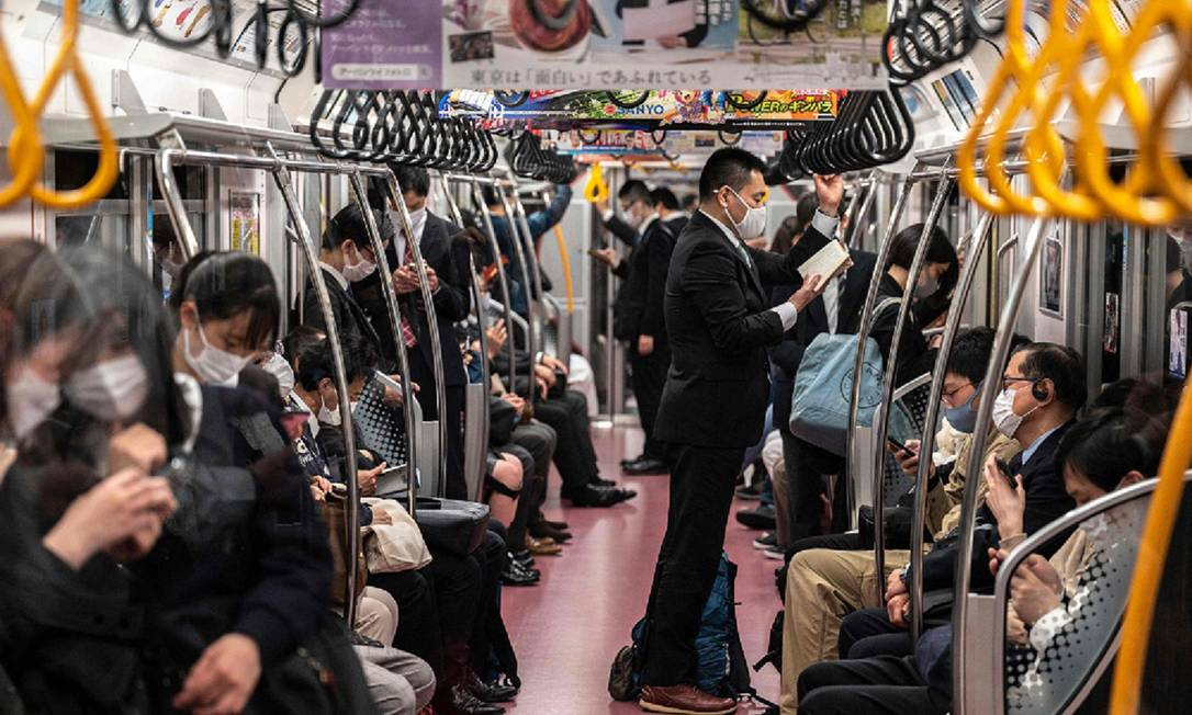 People travel in a train in Tokyo, moments before the announcement of a new state of emergency due to coronovirus Photo: Charlie Tribbleau / AFP