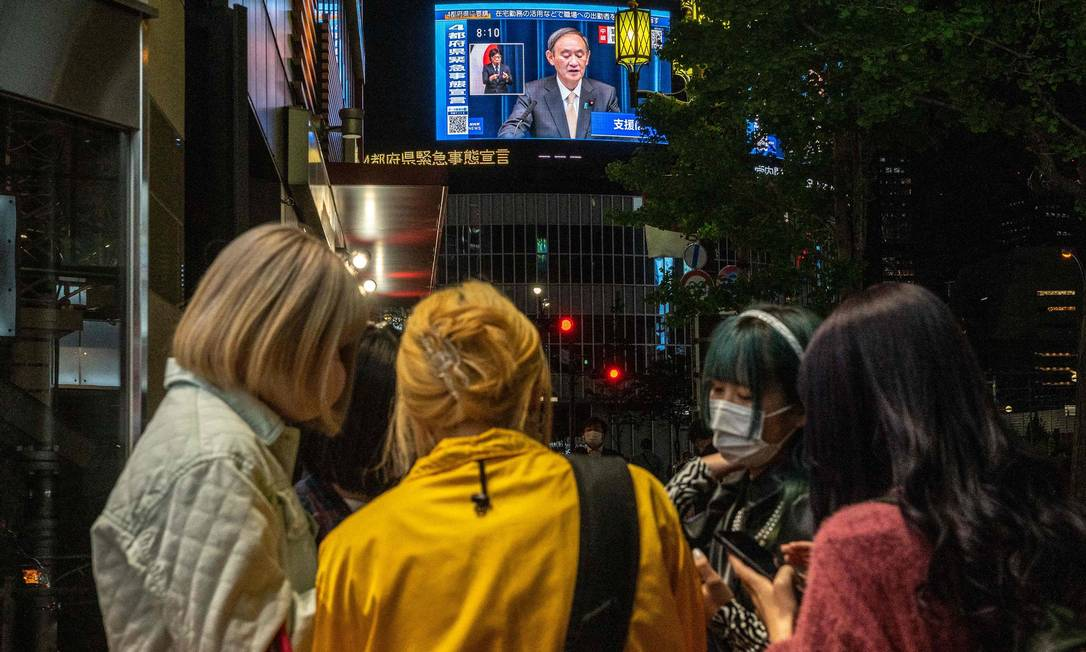 People gather in front of a screen showing Japanese Prime Minister Yoshihide Suga's statement on a new emergency Photo: Philip Fong / AFP