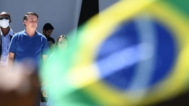 Bolsonaro is seen behind the Brazilian flag and with masked security