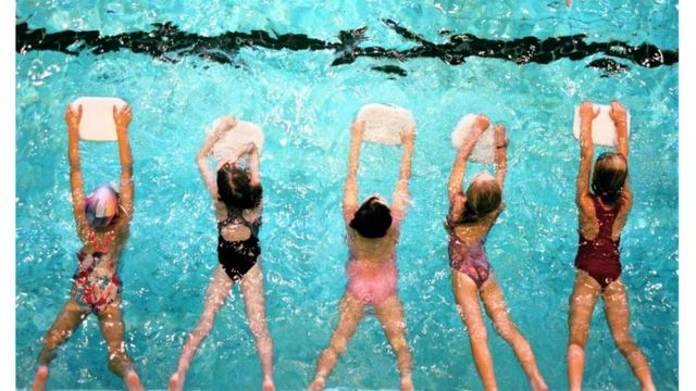 The picture above shows five children in a swimming class using a board