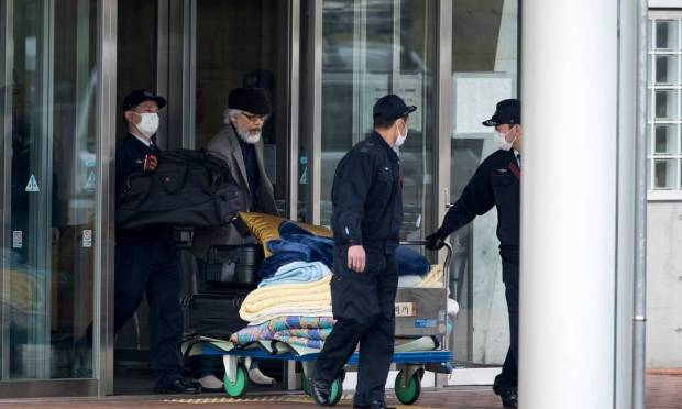Takashi Takano (in a black beret), one of Carlos Ghosn's lawyers, and security guards transport personal property ahead of the release of the former Nissan executive. Photo: Behrouz Mehri / AFP