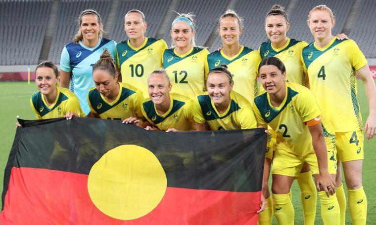 Seleção de futebol feminino da Austrália segura a bandeira aborígene
