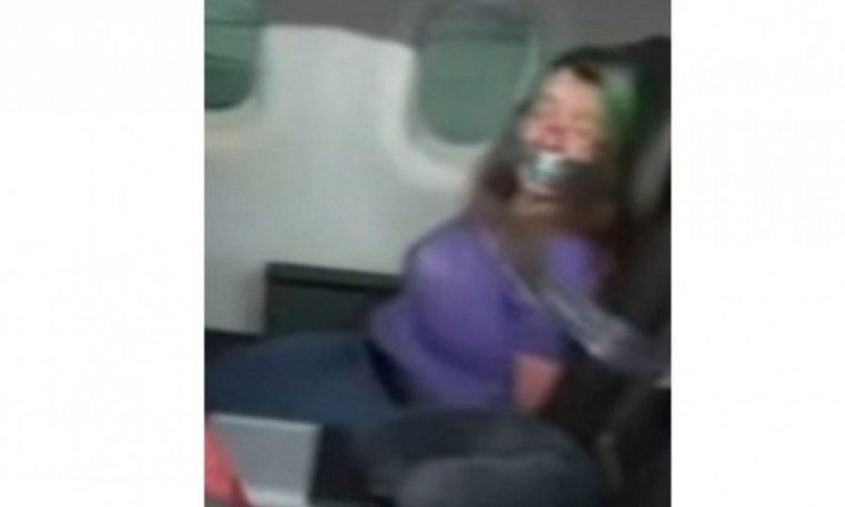 The woman was secured to the plane seat with duct tape after she tried to open the plane doors.  world and science
