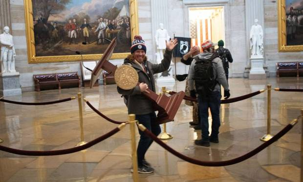 Adam Christian Johnson, 36, a Florida resident, was arrested Friday night (8).  During the riots on Capitol Hill, Adam was seen carrying US House Speaker Nancy Pelosi's pulpit Photo: WIN MCNAMEE / AFP